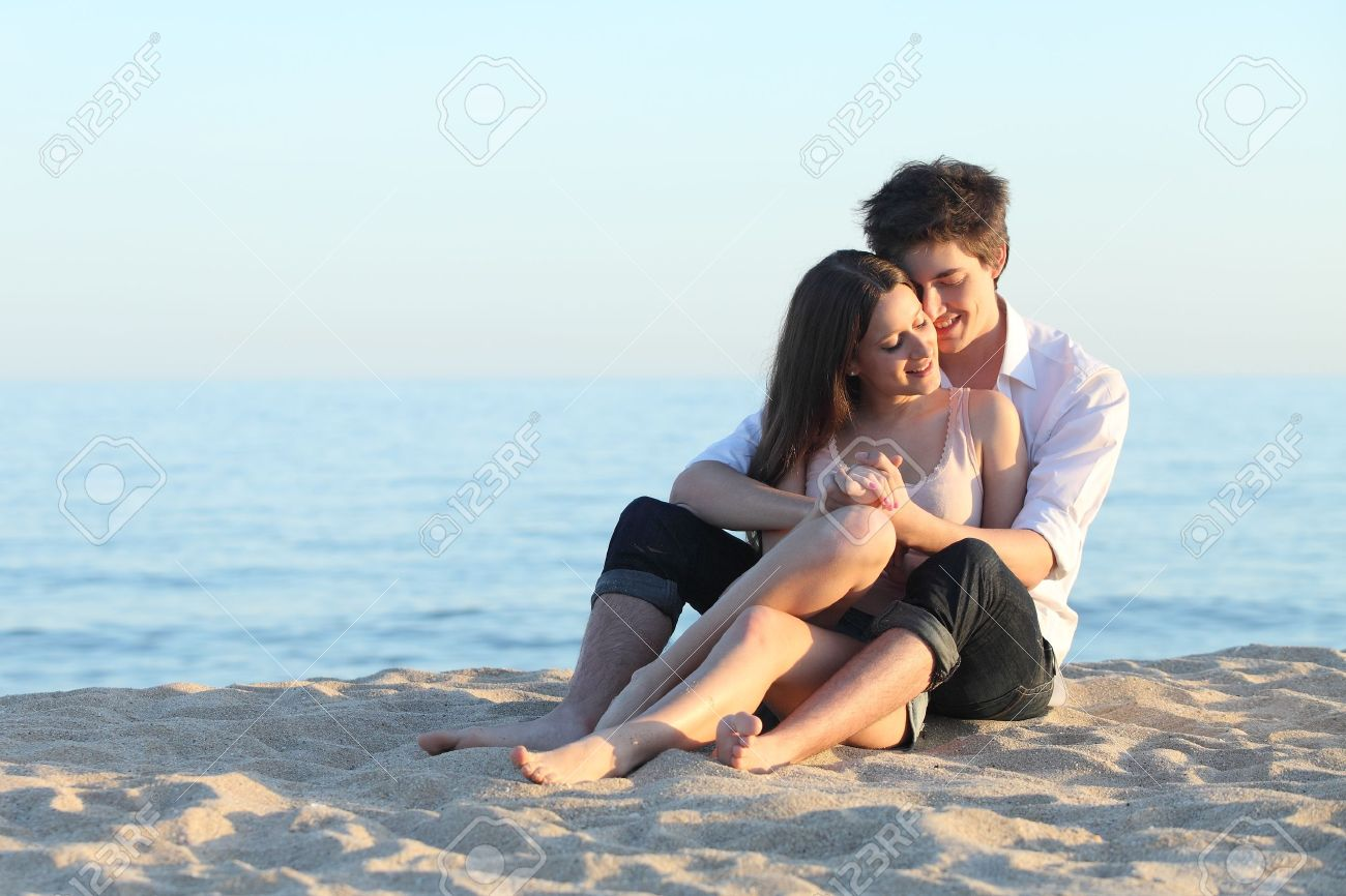 Couple embracing sitting on the sand of the beach with the sea in the background Stock Photo - 19168206