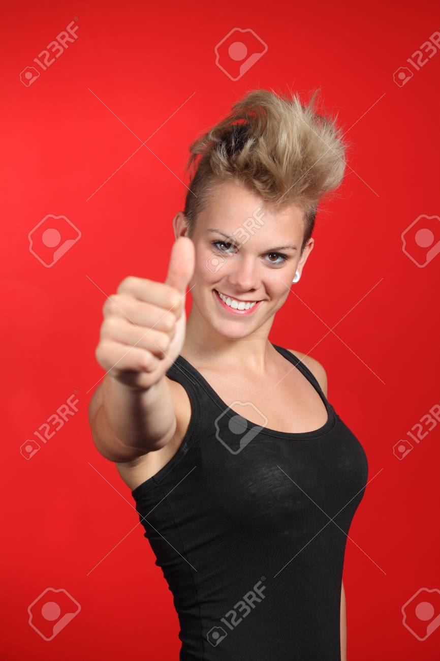 Close up of a fashion teenager girl with thumb up in a red background Stock Photo - 19808346