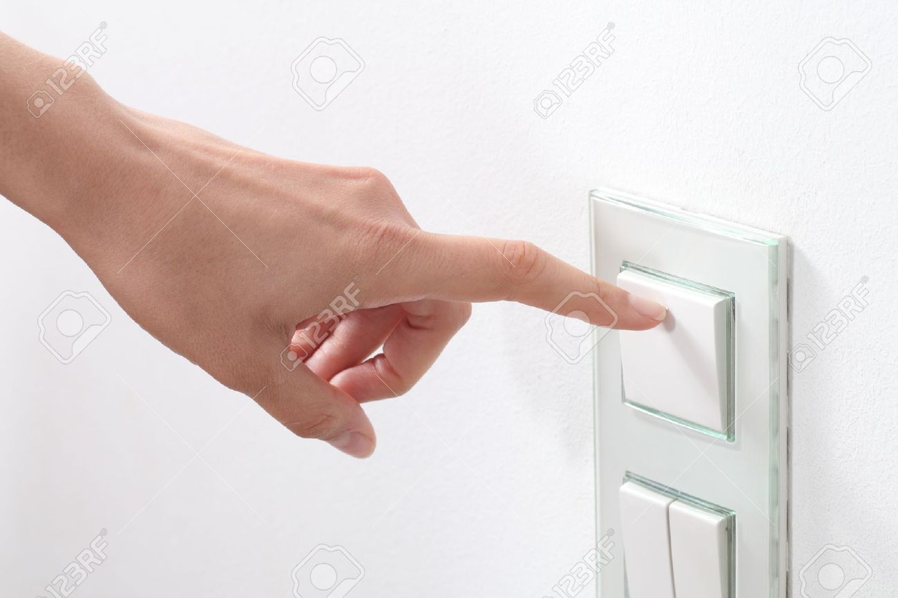 Woman hand turning on the light with a wall switch Stock Photo - 20725971
