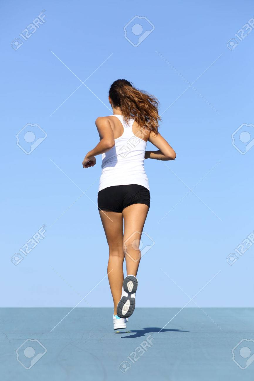 Back view of a fitness woman running on blue with the horizon in the background Stock Photo - 22400860