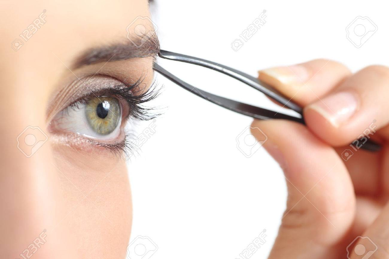 Close up of a woman eye and a hand plucking eyebrows isolated on a white background Stock Photo - 25191646