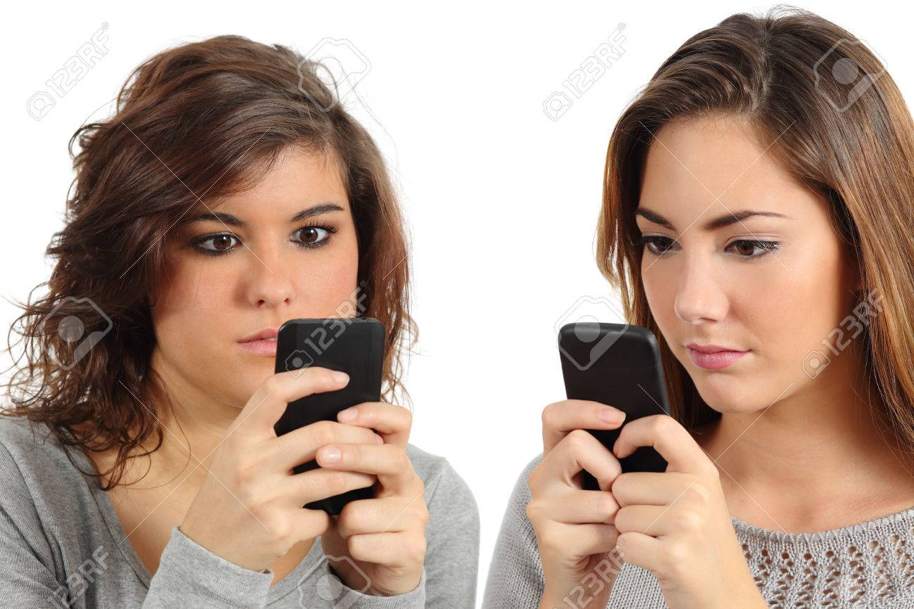 Two teenagers addicted to the smart phone technology isolated on a white background - 25306916
