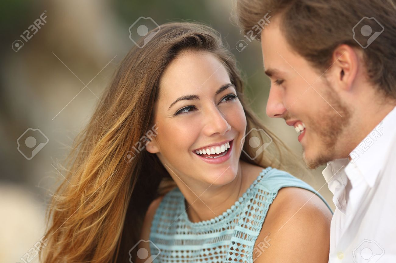 Funny couple laughing with a white perfect smile and looking each other outdoors with unfocused background Stock Photo - 31900636