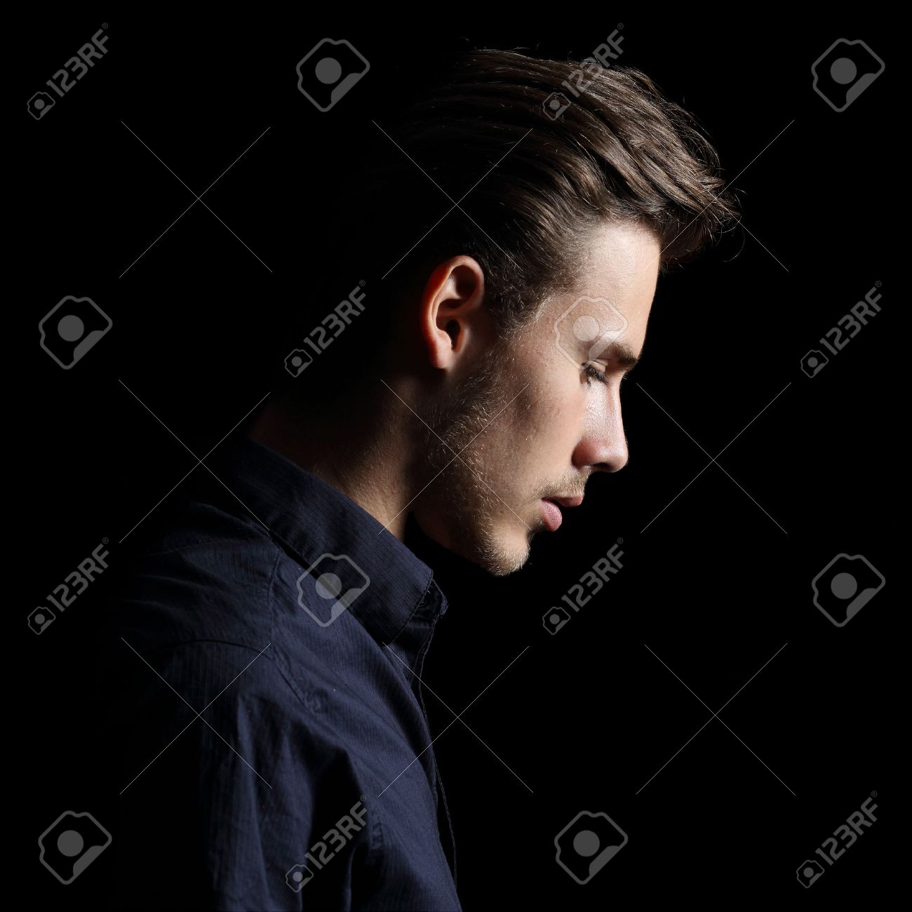 Profile of a sad man face crestfallen on black isolated on a black background stock photo