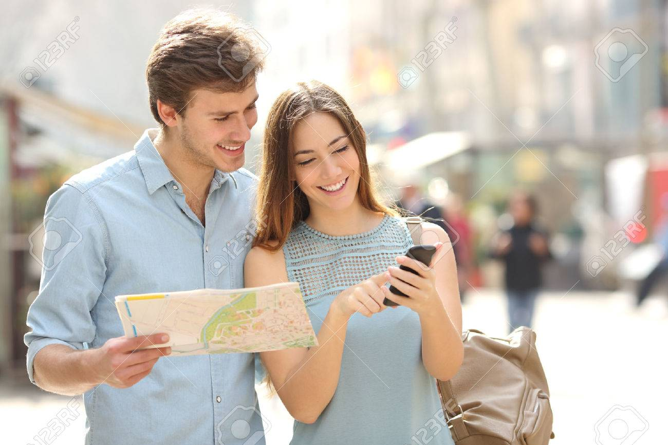 Couple of tourists consulting a city guide and smartphone gps in the street searching locations - 37920170