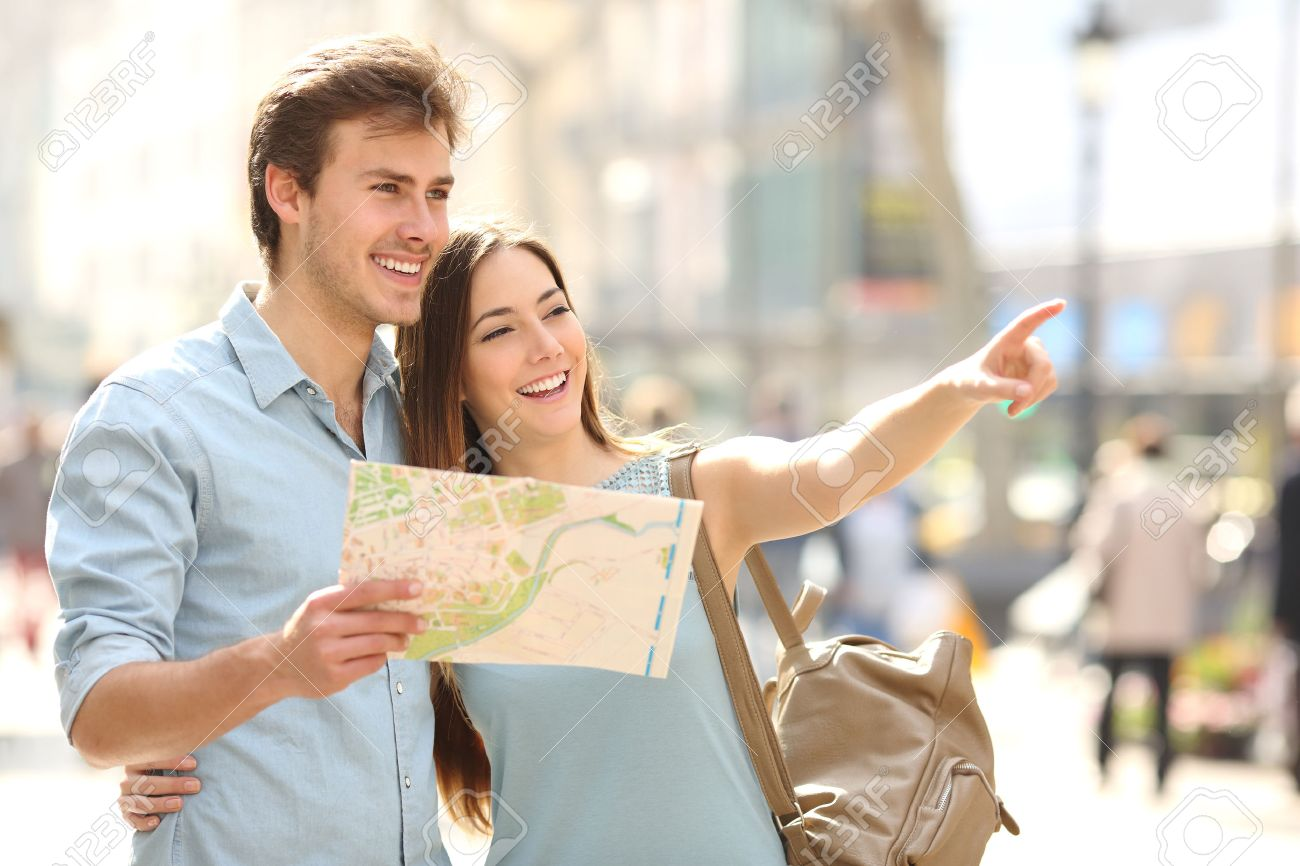 Couple of tourists consulting a city guide searching locations in the street and pointing - 37920171