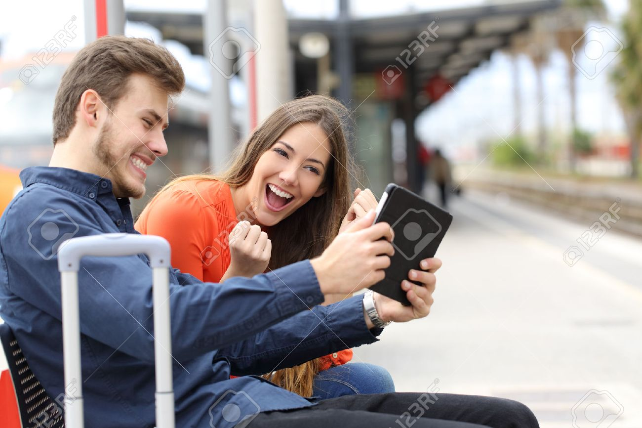 Euphoric couple watching movies or playing games in a tablet in a train station - 40441495