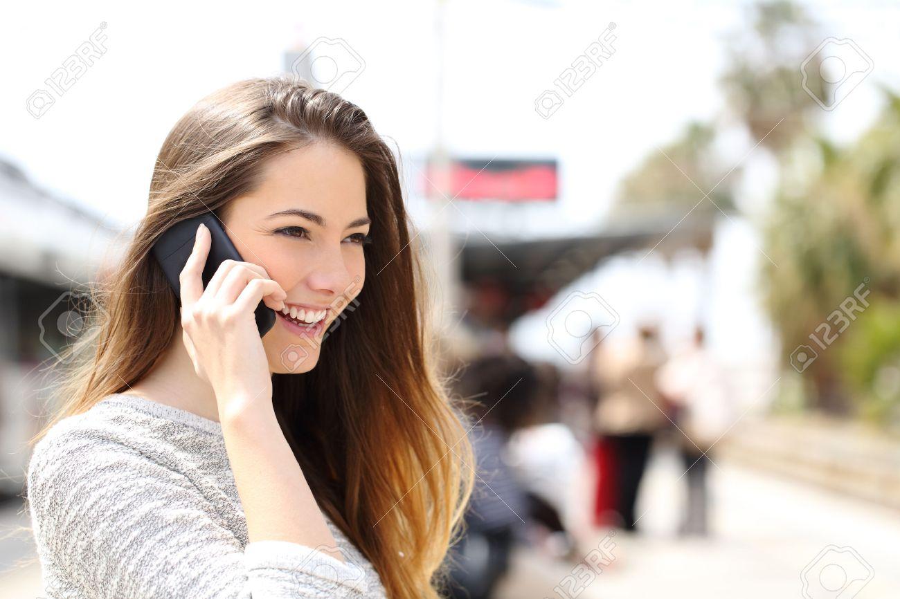 2970f449b3 Archivio Fotografico - Donna parla al telefono prendendo una conversazione  mentre è in attesa in una stazione ferroviaria