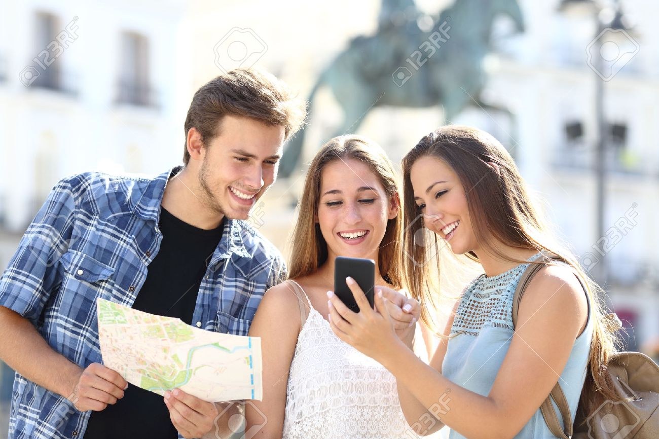 Three tourist friends consulting gps on smart phone in a touristic place with a monument in the background - 44683644