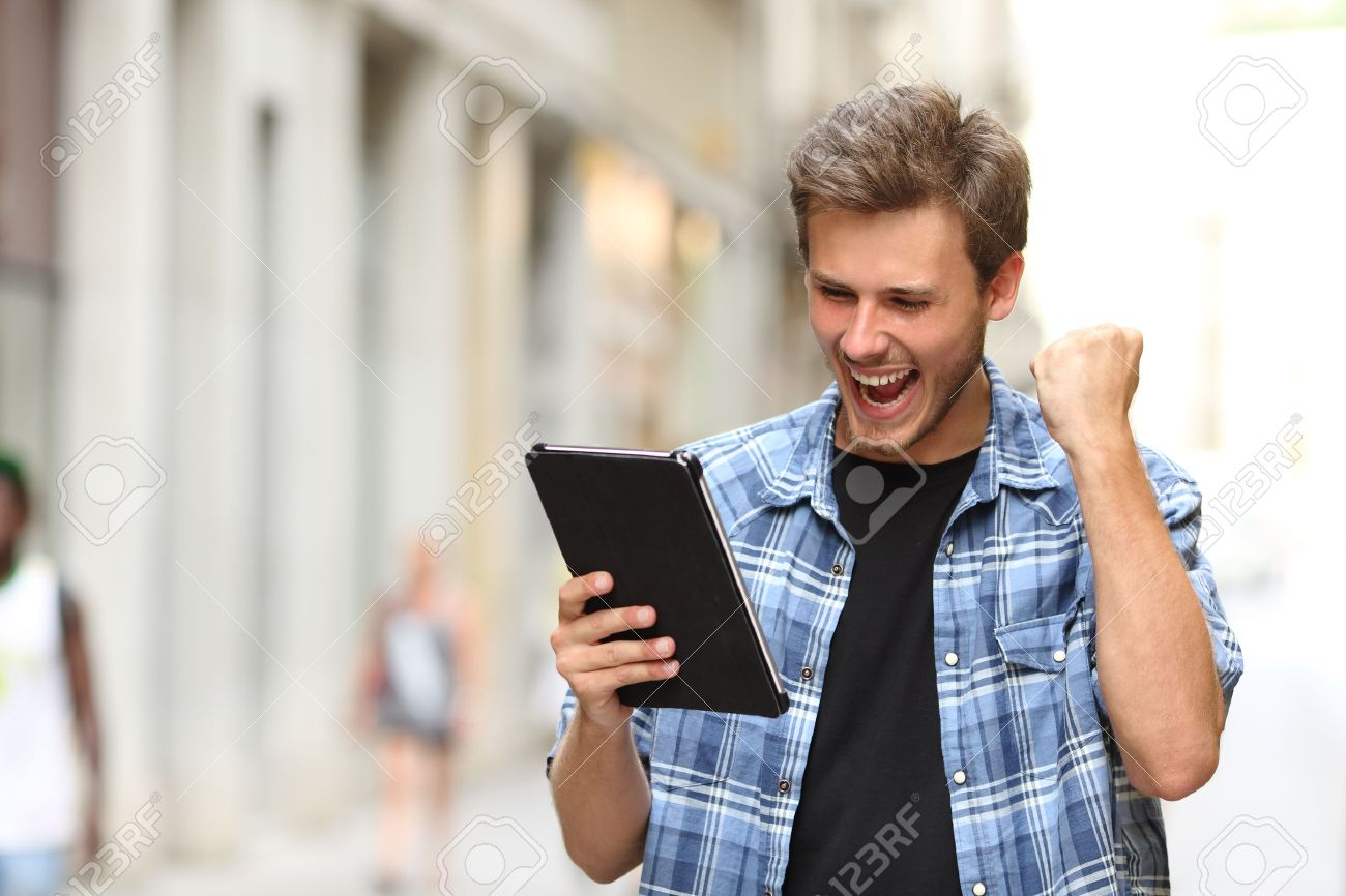 Euphoric winner man screaming with a tablet in the street - 45076829