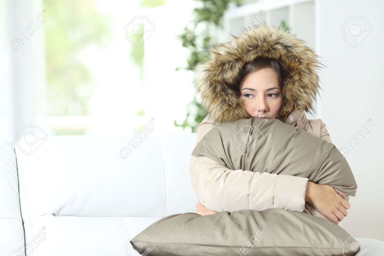 Angry woman warmly clothed in a cold home sitting on a couch - 50531738