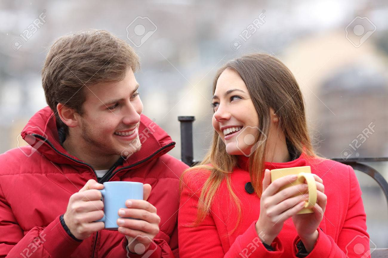 Couple talking relaxed sitting on a bench with coffee cups in winter - 50325495