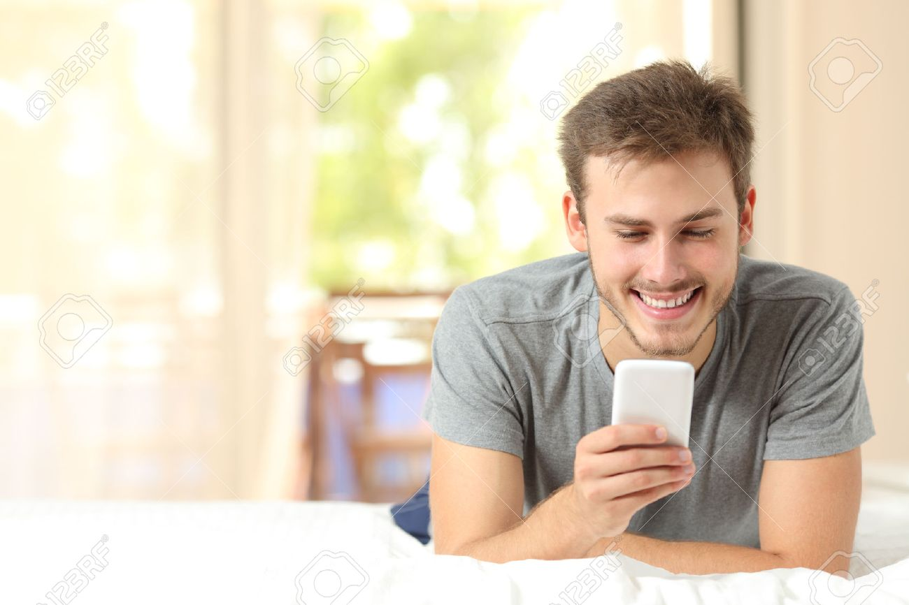 Front view of a guy using a mobile phone in the bedroom at home - 50565659