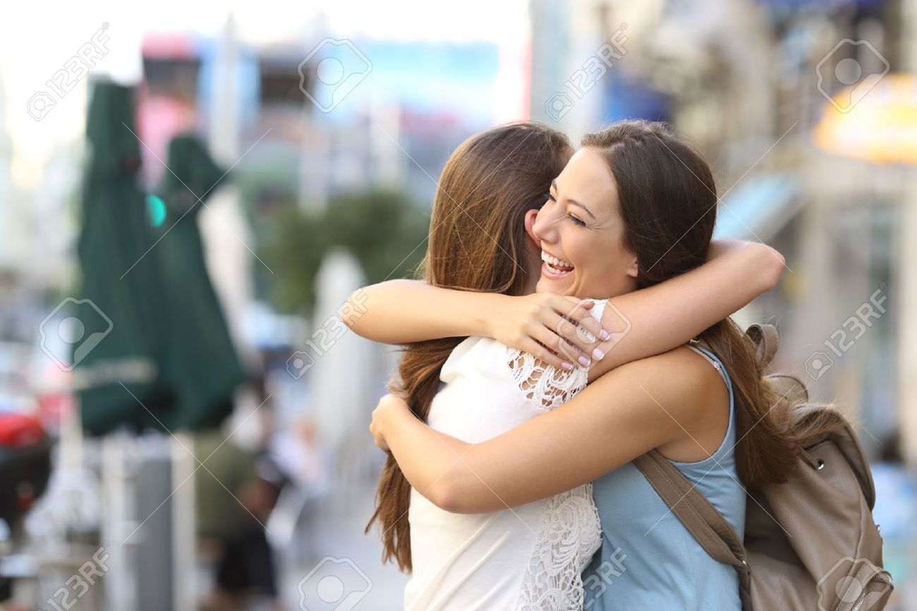 Happy meeting of two friends hugging in the street - 50567140