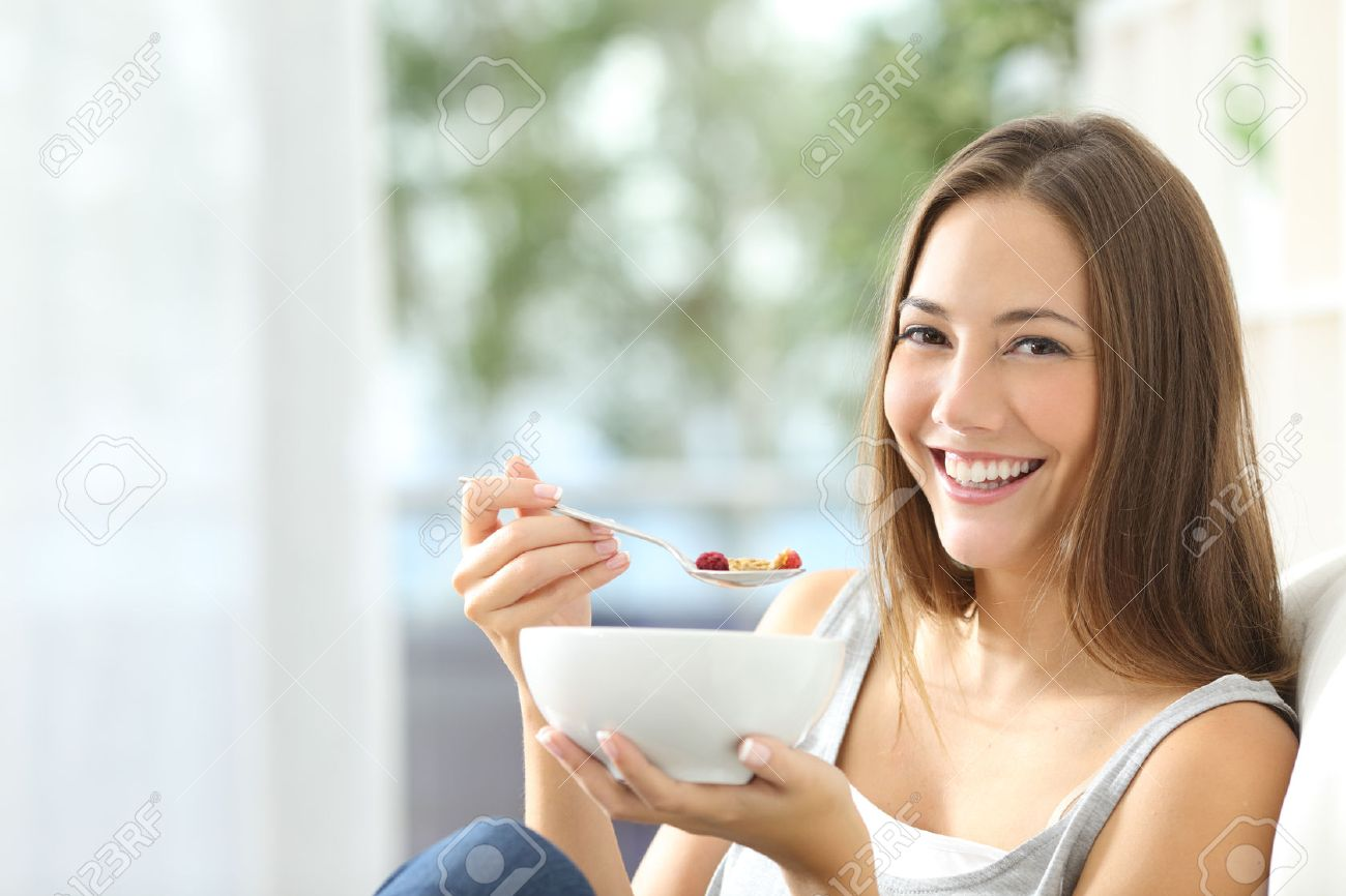 Casual happy woman dieting and eating cornflakes sitting on a couch at home - 50532323