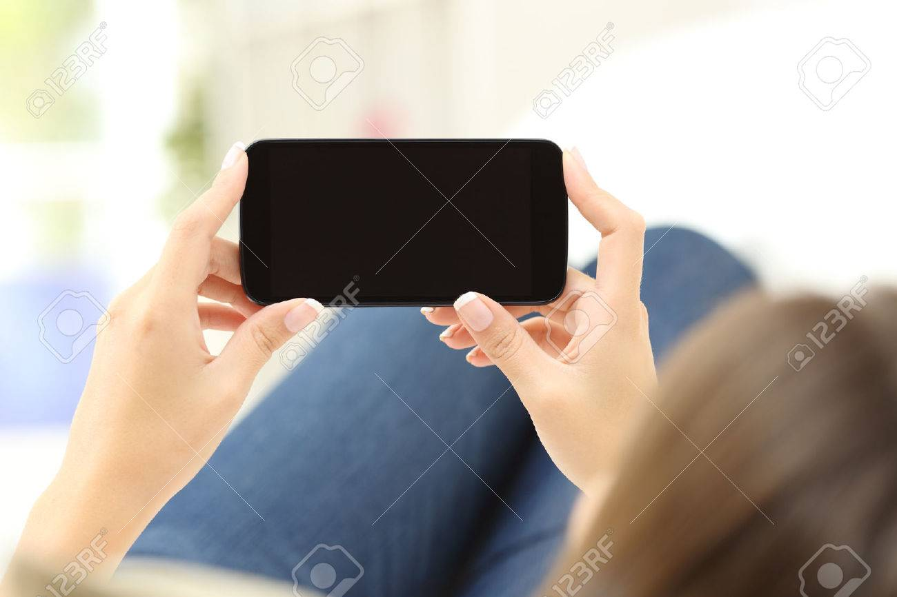 Back view of a close up of a woman hands watching media in a smart phone lying on a couch at home - 50532387
