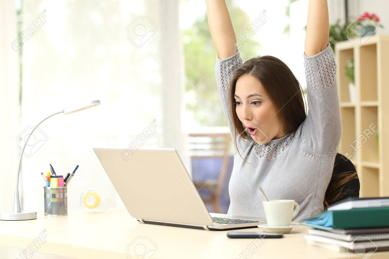 Euphoric and surprised winner winning online watching a laptop at home - 50532397