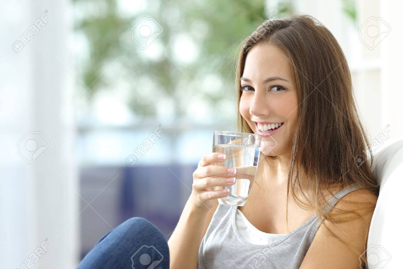 Girl drinking water sitting on a couch at home and looking at camera - 50532402