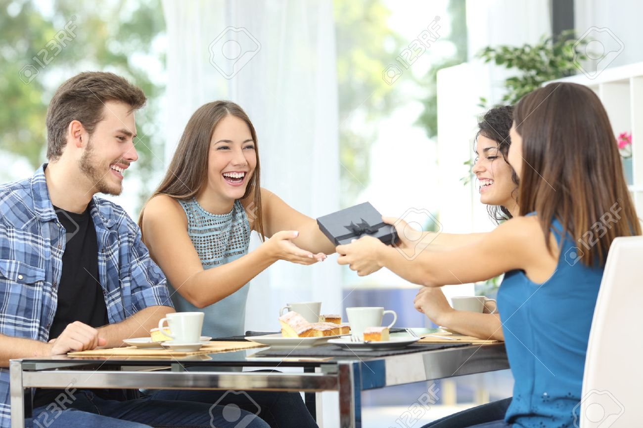 Friends celebrating birthday and giving gift to a girl sitting in a dining room - 51824889