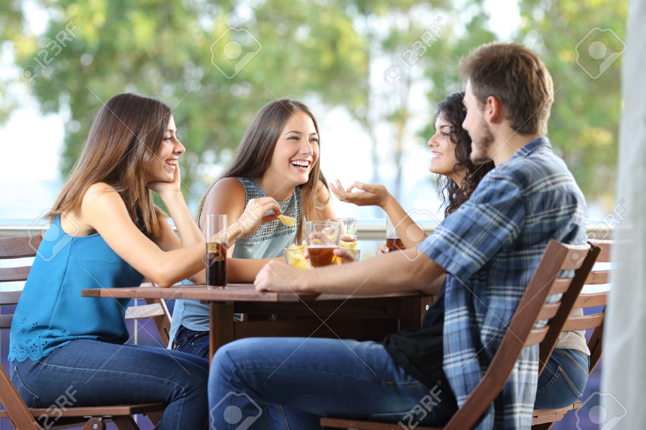 Group of four friends talking and drinking sitting in a terrace at home - 51824821