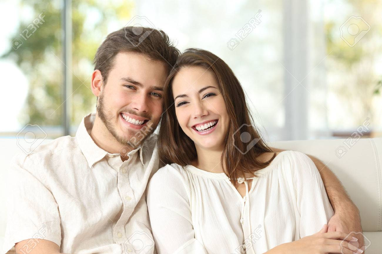 Happy couple sitting on a couch at home and looking at camera - 52407680