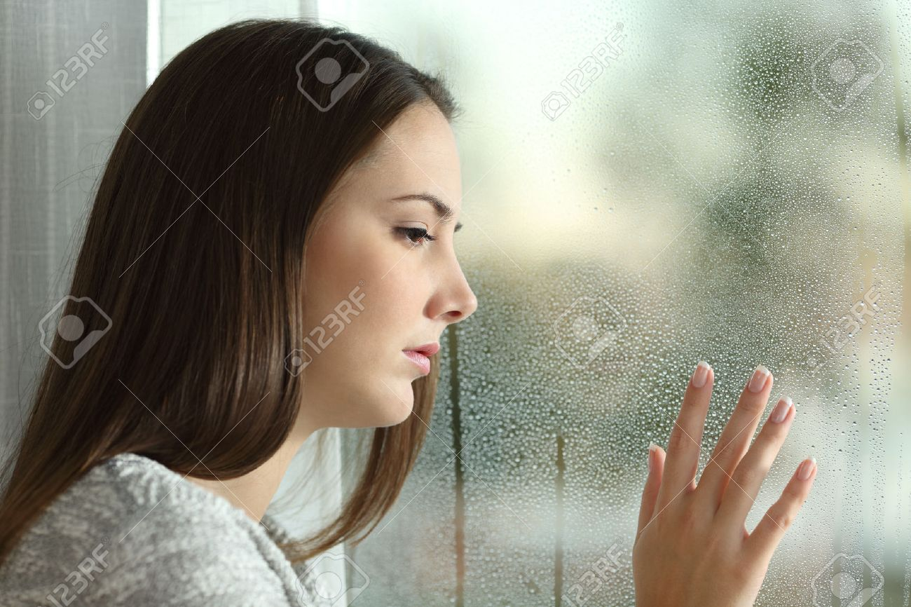 sad woman looking the rain falling through a window at home or