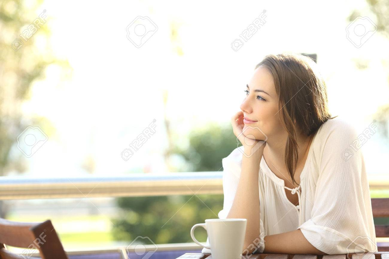 Pensive happy woman remembering looking at side sitting in a bar or home terrace - 52549295