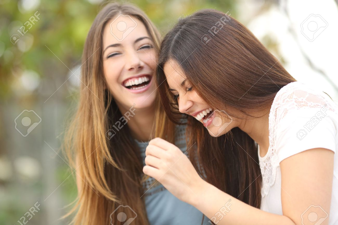 Two happy woman friends laughing together in a park with a green background - 54069519