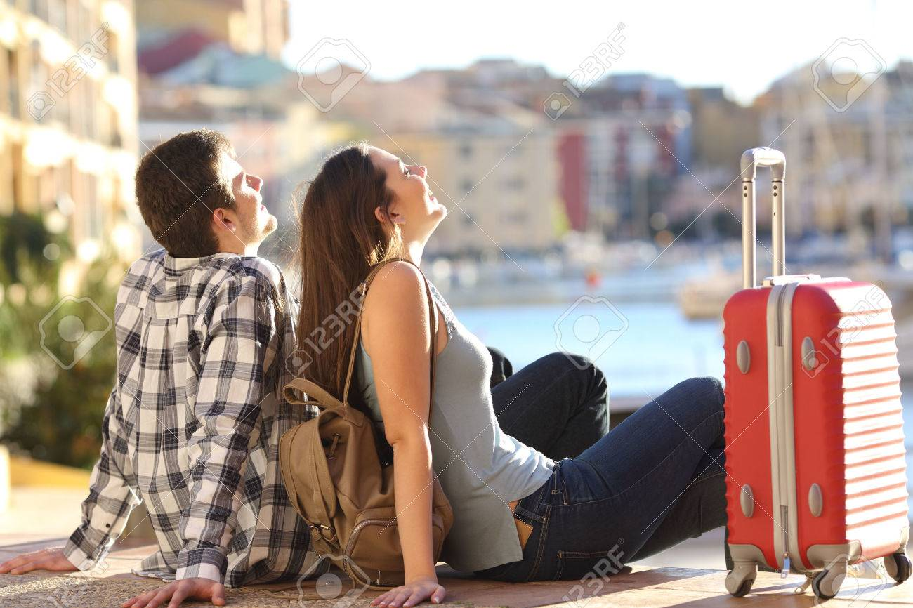 Side view of a couple of 2 tourists with a suitcase sitting relaxing and enjoying vacations in a colorful promenade. Tourism concept - 56102111