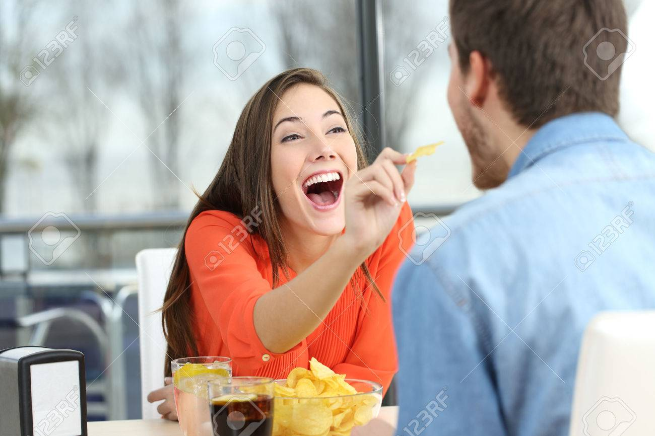Playful couple eating chip potatoes and joking looking each other in a date in a coffee shop - 56102144