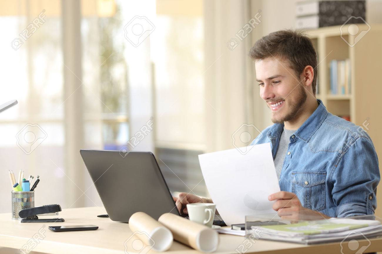Entrepreneur working with a laptop and holding a document in a little office or home - 59038730