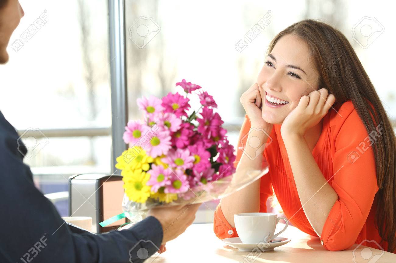 Candid woman dating in a coffee shop and looking her boyfriend who gives her a bunch of flowers - 59199388