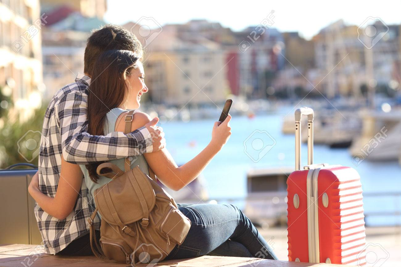 Couple of tourists sitting searching information or booking an hotel on a smart phone on vacations - 64632627