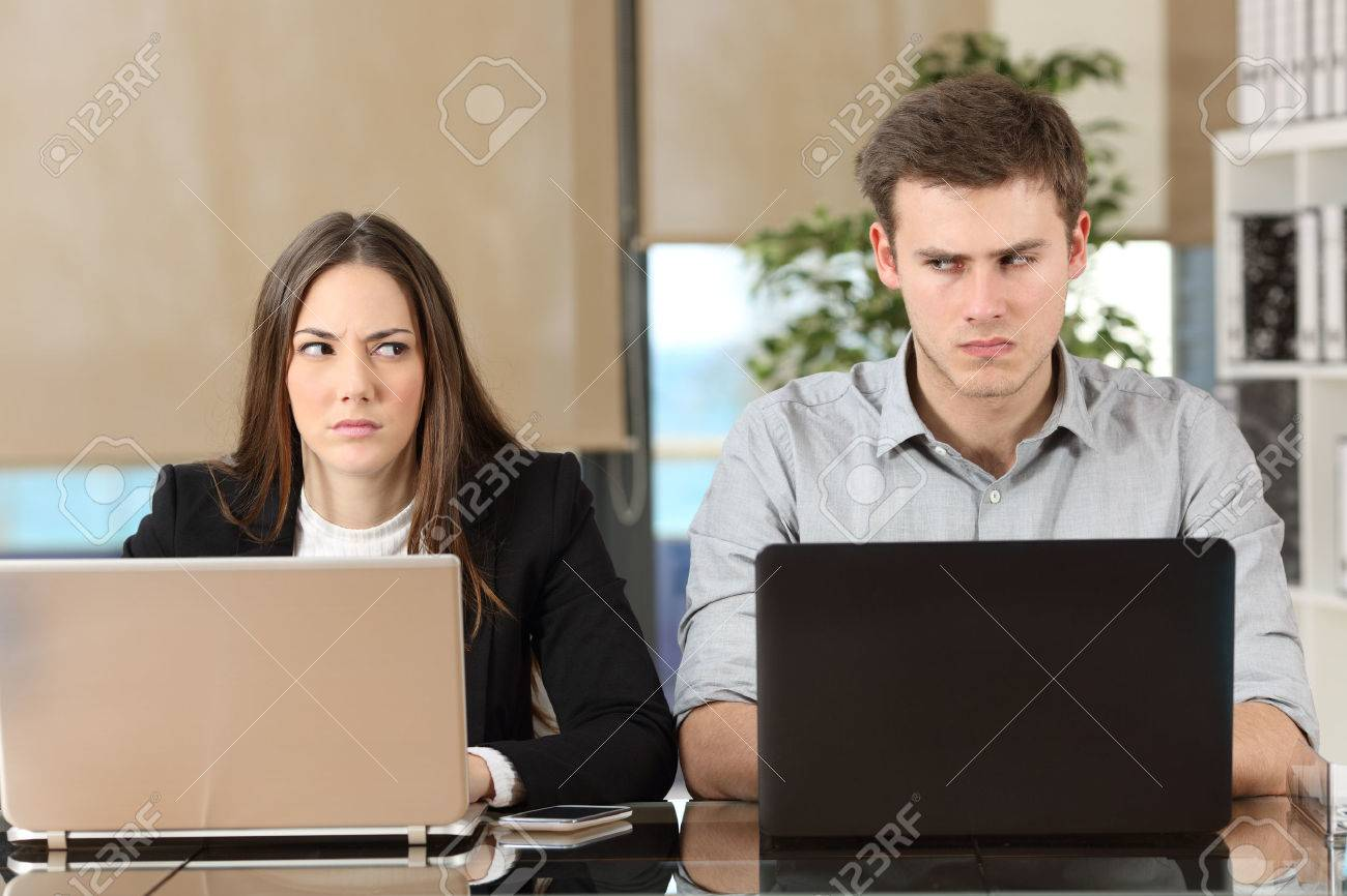 Front view of two angry businesspeople using computers disputing at workplace and looking sideways each other with envy - 61935133