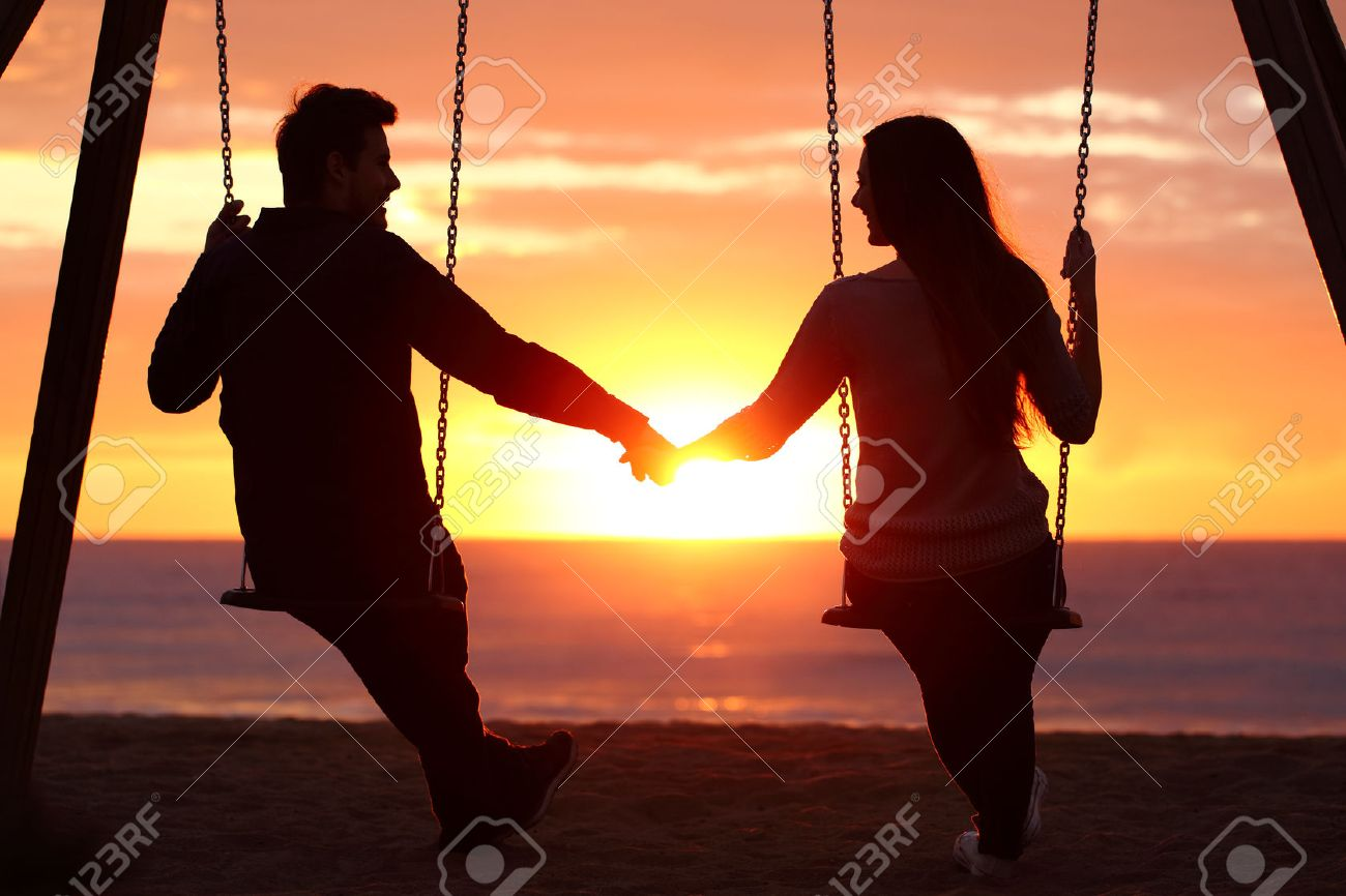 back light portrait of a couple silhouette sitting on swing holding