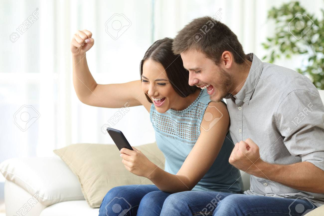 Excited couple watching media content together using a mobile phone sitting on a couch in the living room of a house - 68711024