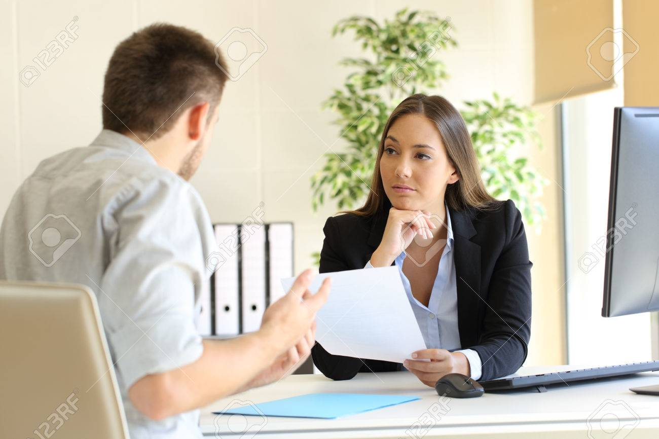 Man searching employment in a bad job interview with the interviewer looking mistrustful - 68878914