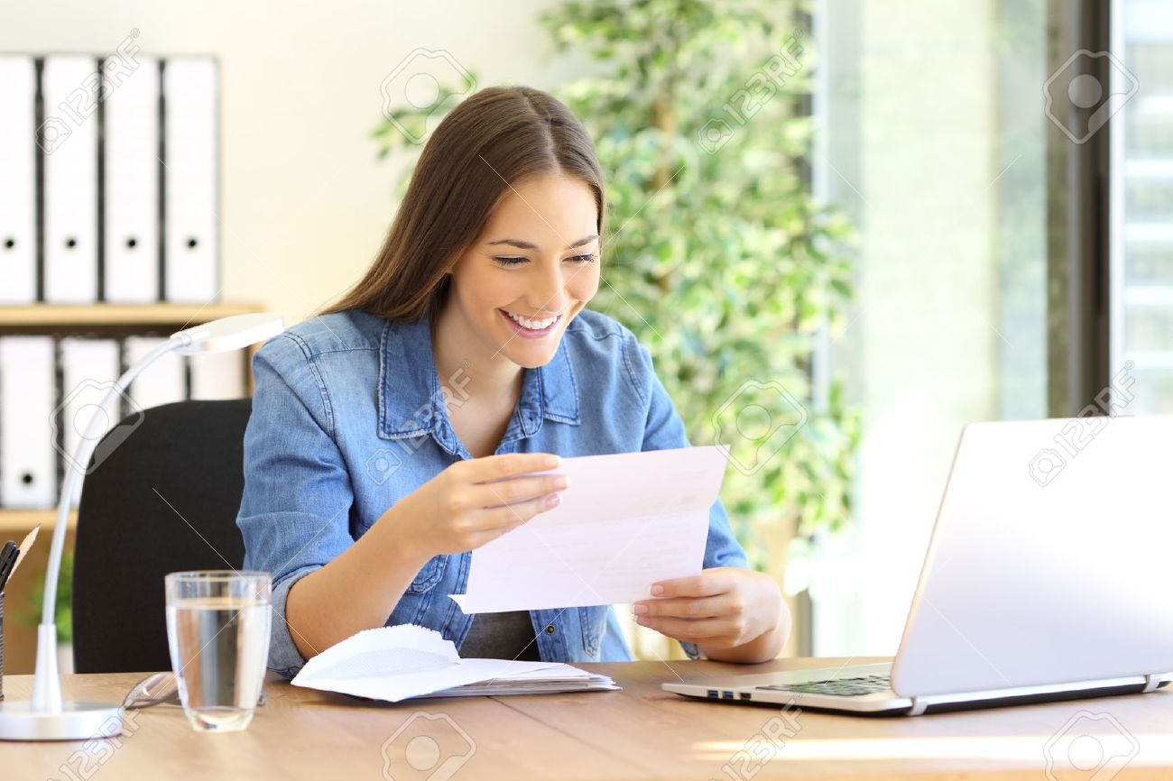 Happy entrepreneur woman reading good news in a letter in a desk at office - 69033524