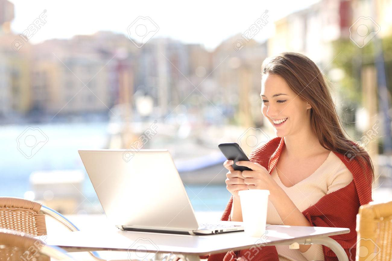 Girl using a smart phone and a laptop in a bar or hotel terrace with a port in the background - 71225900