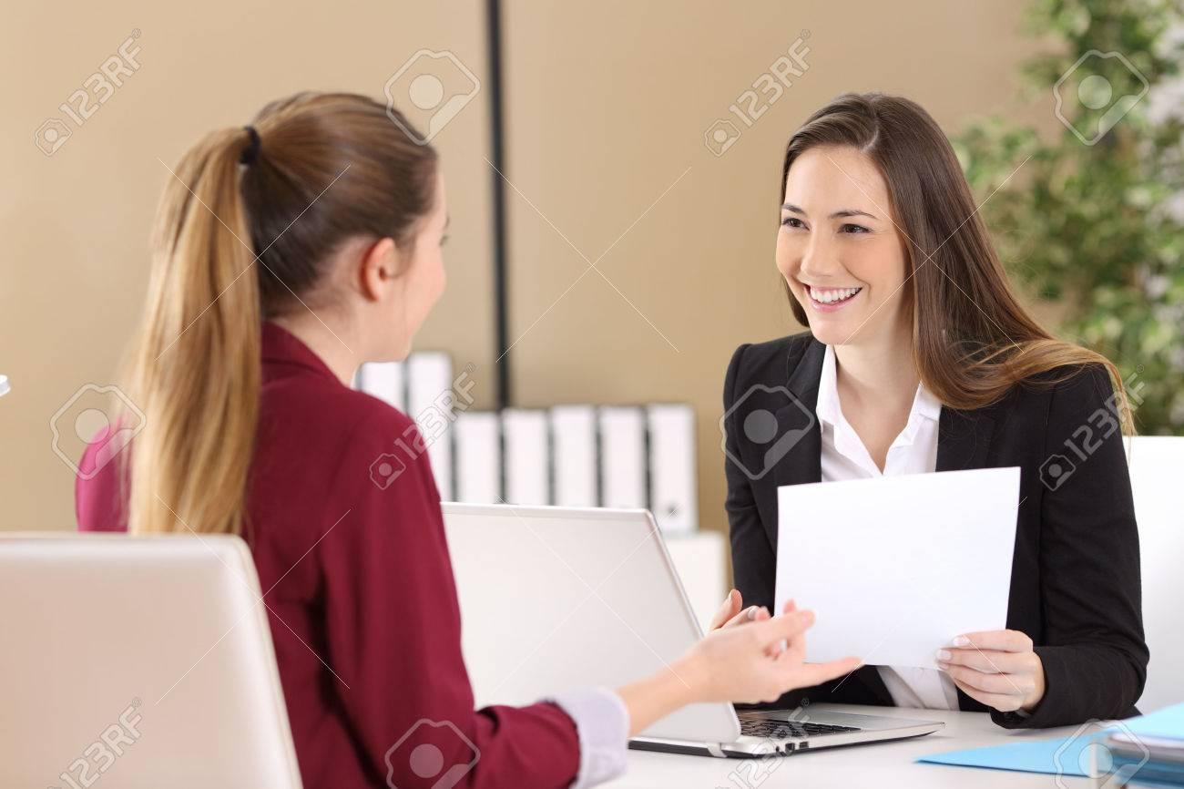 Boss attending to an employee during a job interview in a desktop at office - 73044748