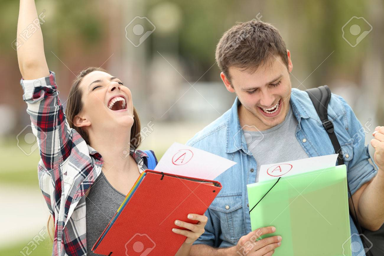 Two excited students with approved exams in the street - 82074326