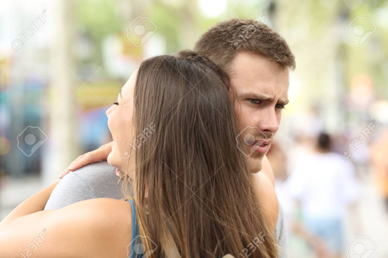 Discontent boyfriend hugging his partner on the street - 84207902