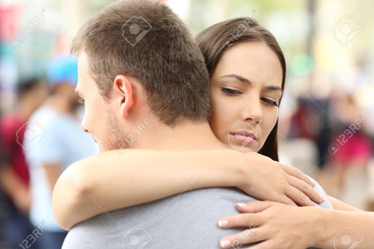 Discontent girlfriend hugging her partner on the street - 84208418