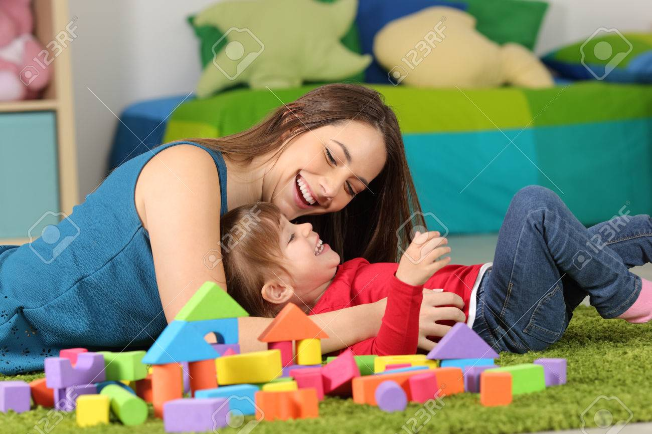 Mother or nanny playing with a child on the carpet in a room at home - 84176781
