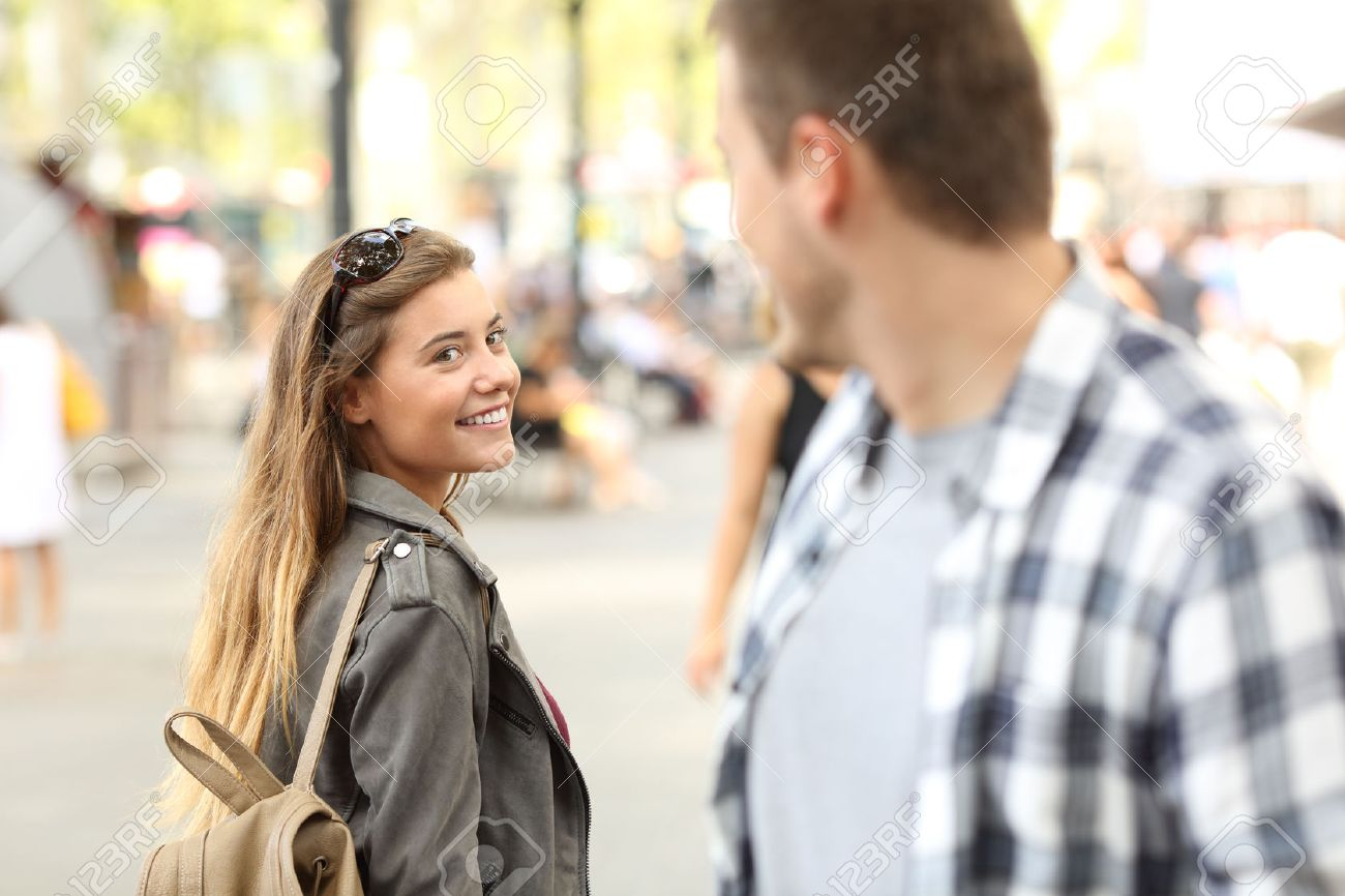 Strangers girl and guy flirting looking each other on the street - 84651481