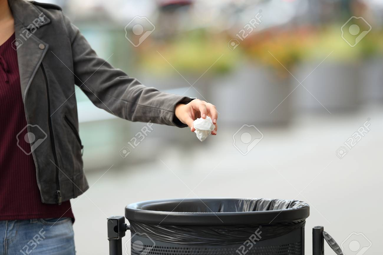 Close up of a lady hand throwing garbage to a trash bin on the street - 88075436