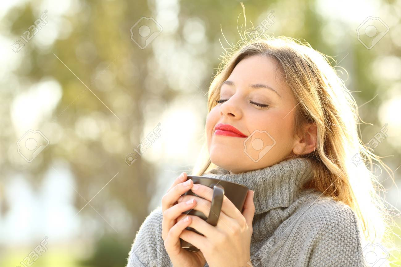 Portrait of a relaxed girl wearing jersey holding a cup of coffee and breathing outdoors in a park in winter - 89613803
