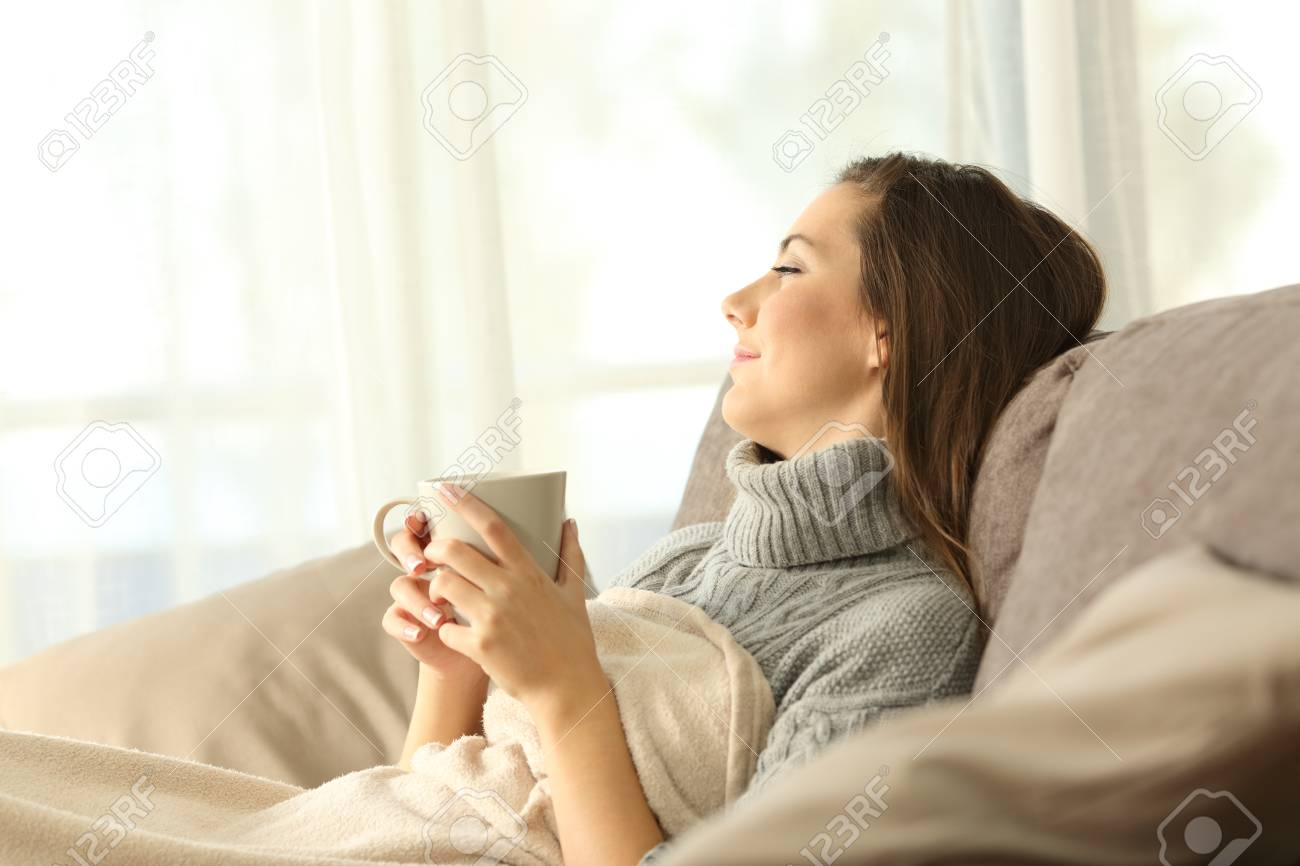 Portrait of a pensive woman relaxing sitting on a sofa in the living room in a house interior in winter - 91215588