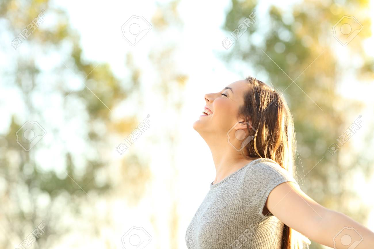 Side view portrait of a woman breathing fresh air outdoors in summer with trees and sky in the background - 91196498