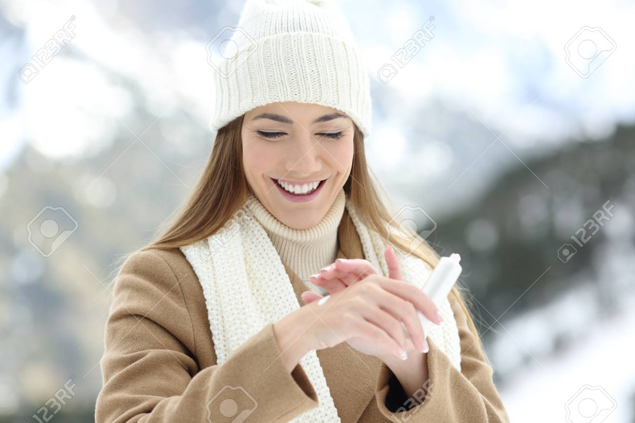 Front view portrait of a happy woman applying moisturizer cream to hydrate hands with a snowy mountain in the background - 91383648